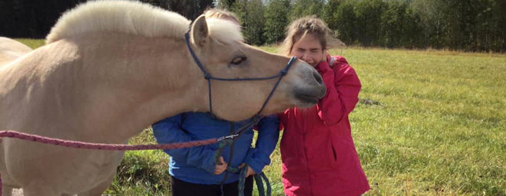Metsolan palvelukeskuksen asukas silittää hevosta.