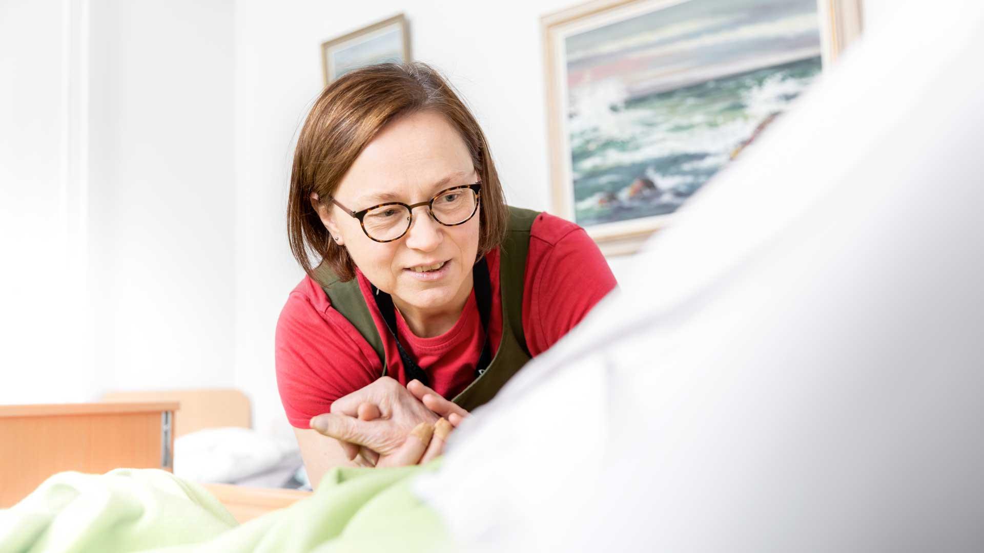 Sairaanhoitaja Minna Rantapää potilaan vuoteen ääressä.